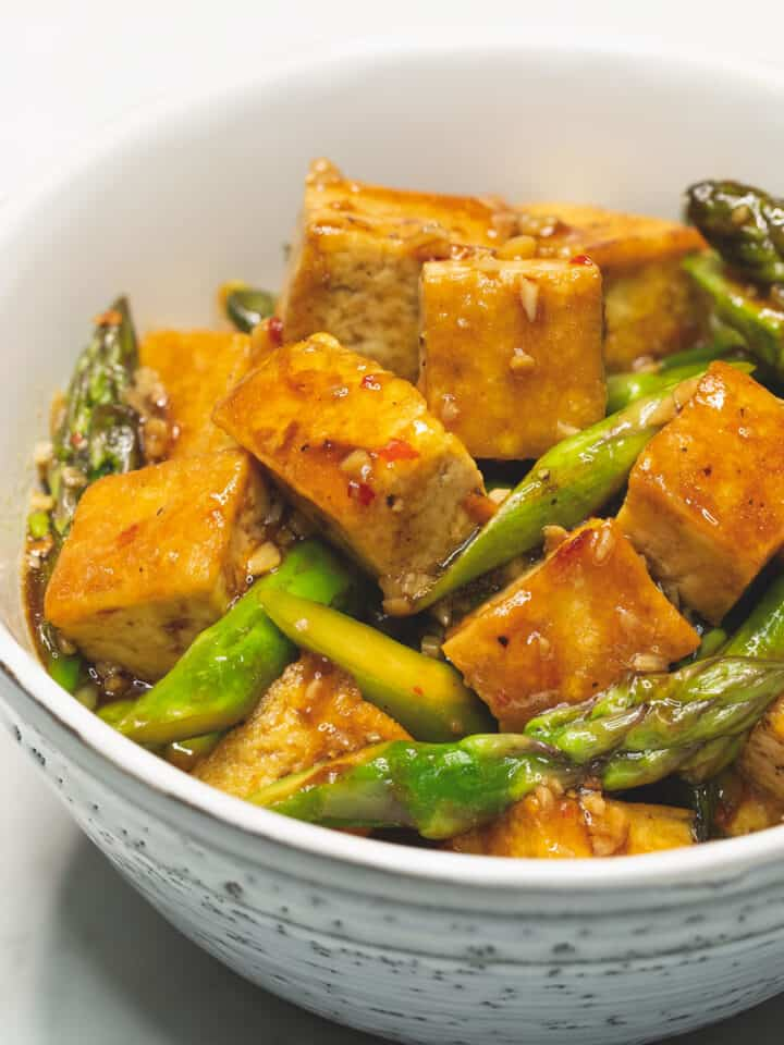 tofu and asparagus stir fry in a bowl