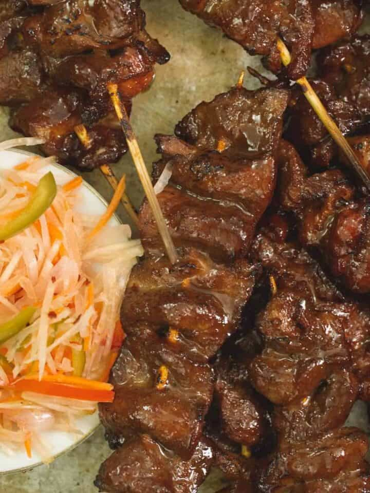 barbecue pork skewers on a plate served with achara