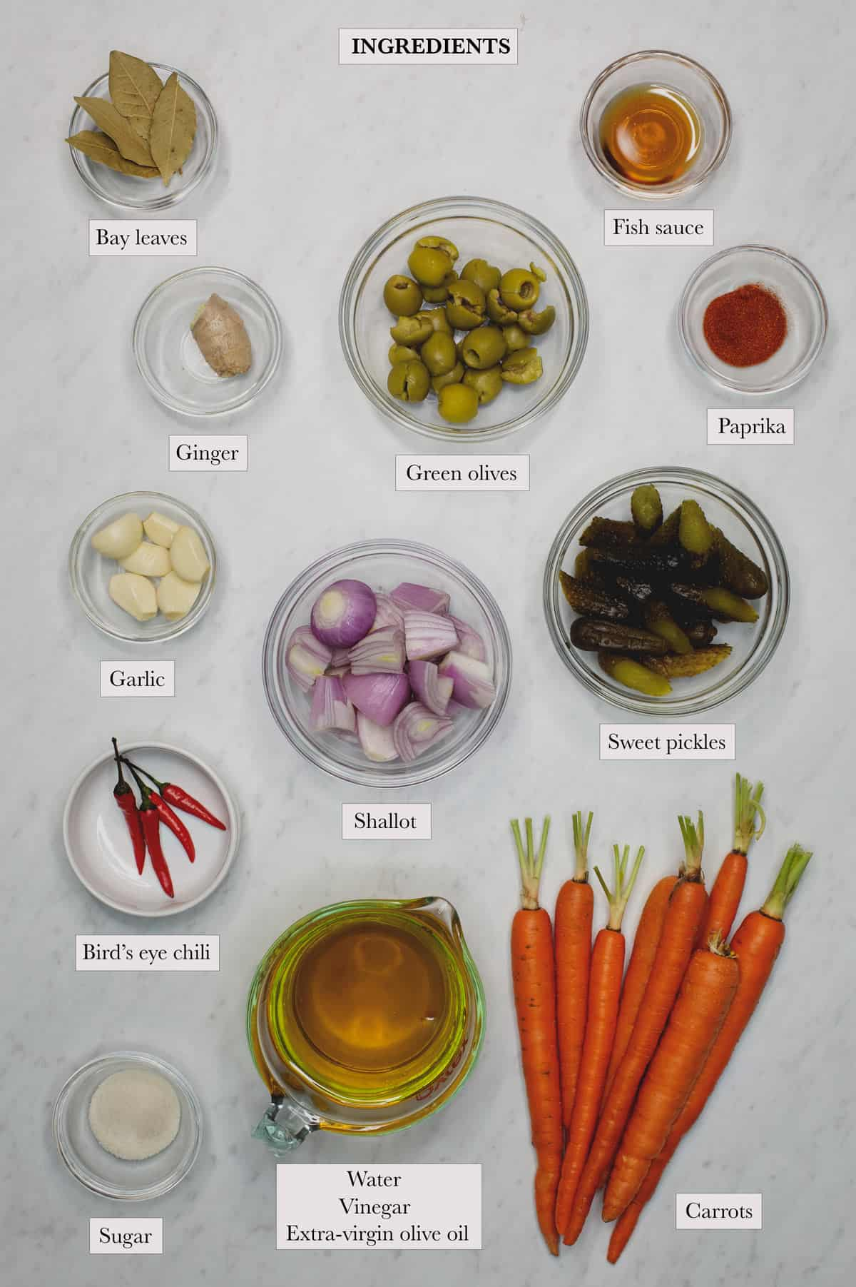 ingredients include carrots, sweet pickles, shallot, garlic, olives, bay leaves, ginger, sugar, bird's eye chili, fish sauce, paprika, water, vinegar, and extra-virgin olive oil.