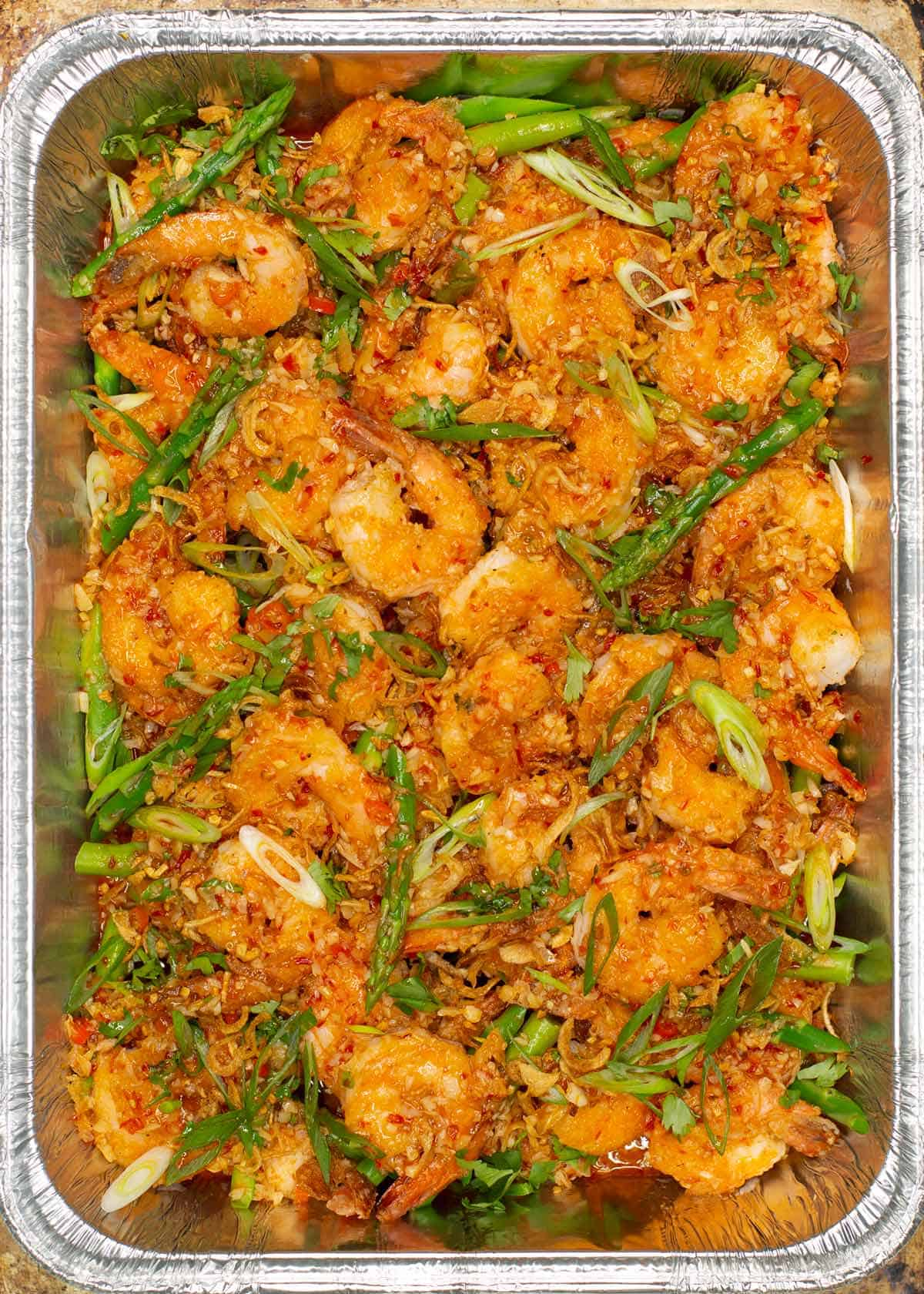 Asian Chili Garlic Shrimp with asparagus served on a foil pan