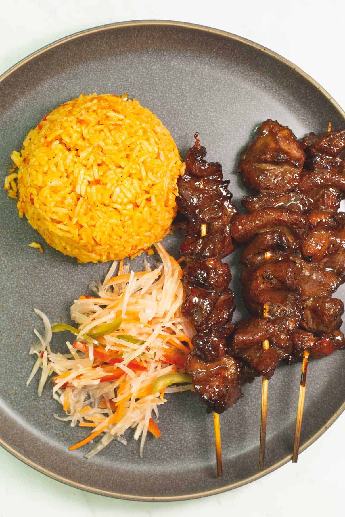 barbecue pork skewers on a plate served with java rice and achara