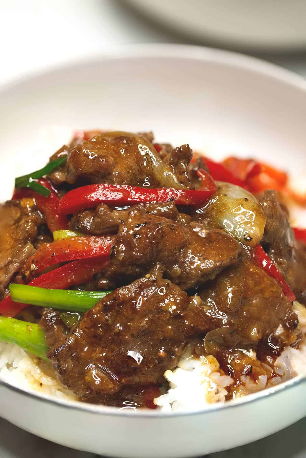 A serving of beef stir fry with onions and peppers over rive in a bowl.