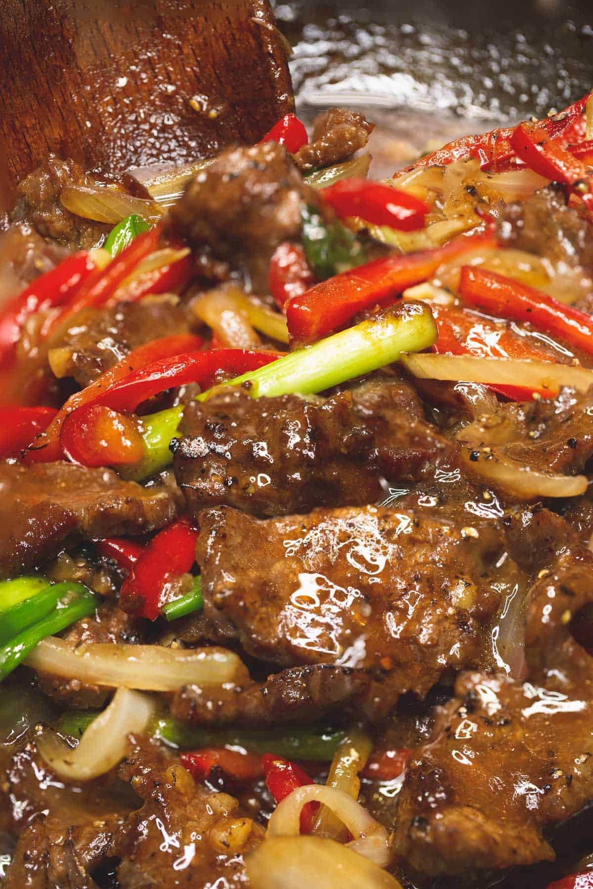 Beef stir fry with onions and peppers in a wok with a wooden spoon.