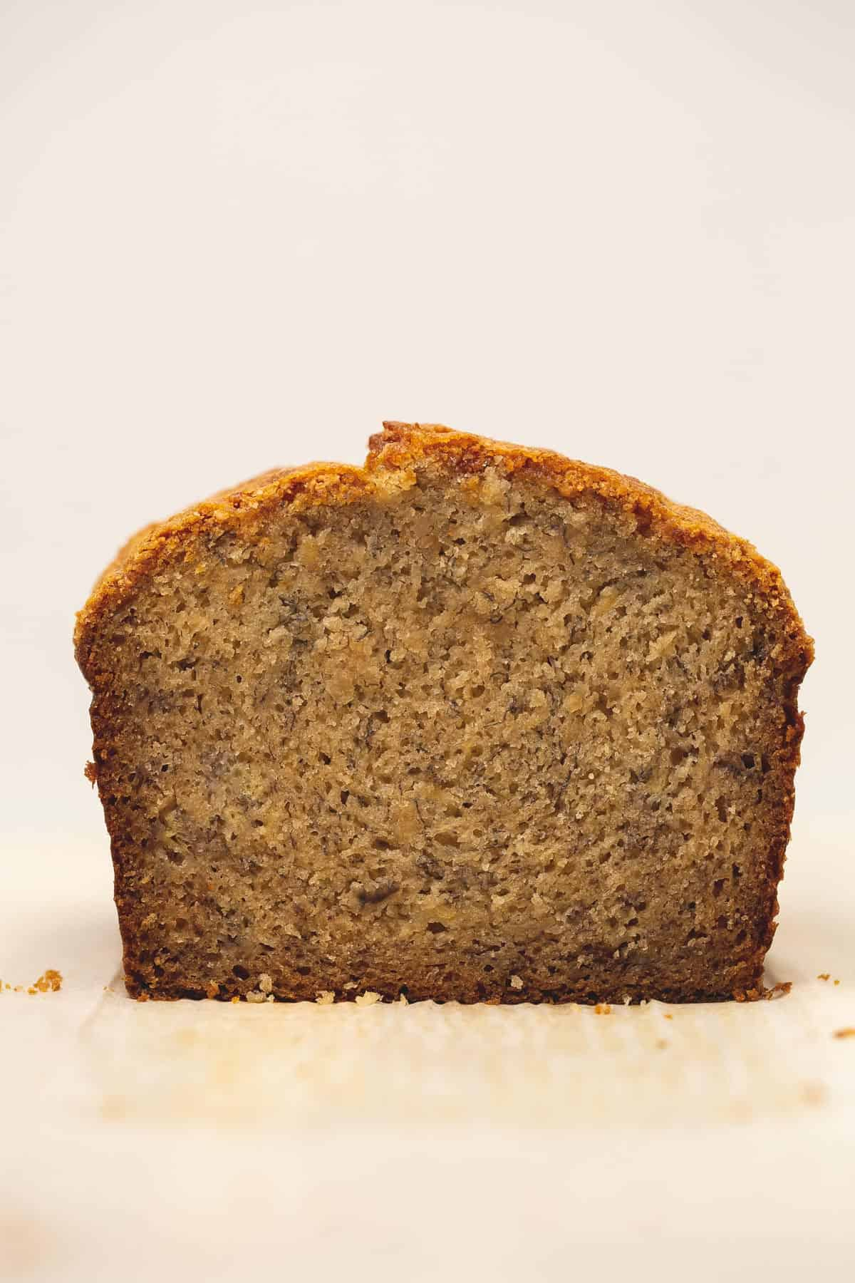A cross section of banana bread on a parchment paper.