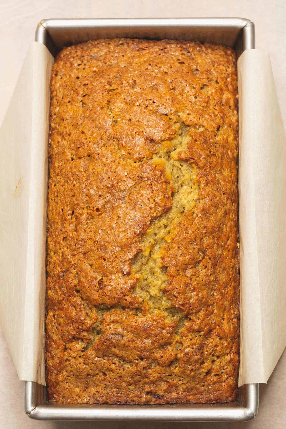 A loaf of banana bread in a parchment paper lined pan.