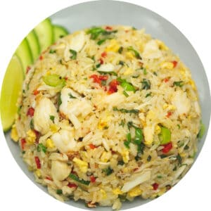 crab meat fried rice on a plate with sliced cucumbers and lime wedge on the side